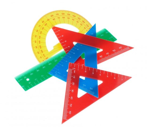 Satz geometrische werkzeuge lineale, dreieck, winkelmesser. an einer weißen wand.