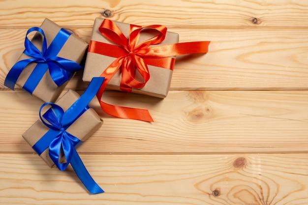 Satz geschenkboxen in bastelpapier eingewickelt und roter satin und blaues band binden