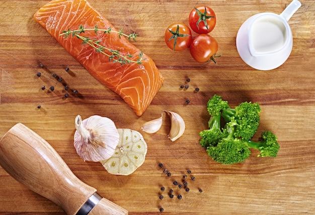 Satz gesundes antikrebsfutter auf holztisch. roter lachsfisch, brokkoli, knoblauch, milch, pfeffer und tomaten auf einem tisch verteilt. gesundes mahlzeitkonzept, draufsicht