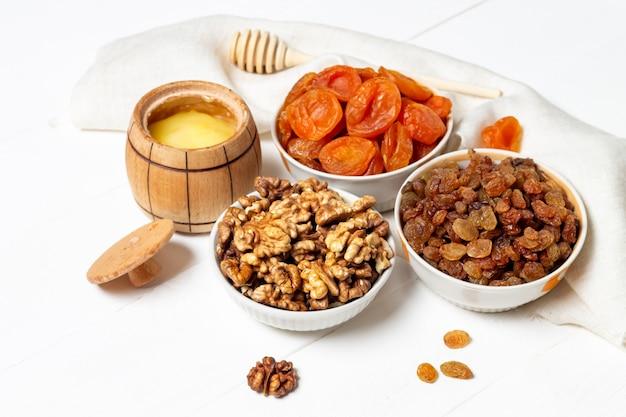 Satz getrocknete beeren, früchte und nüsse, die in einem teller liegen (walnüsse, kürbis, kirsche, aprikose, apfel, datteln)