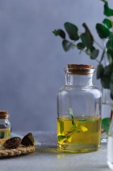 Satz glasflaschen mit eukalyptusätherischem öl auf grauer tabelle verlässt im vase