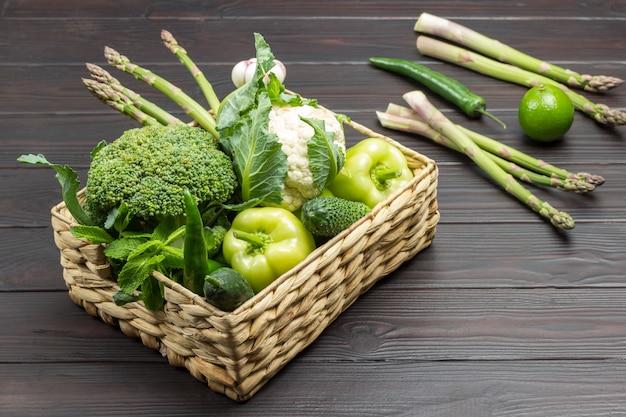 Satz grünes gemüse im rattankorb. spargel, limette und pfeffer auf dem tisch. hölzerner hintergrund. ansicht von oben