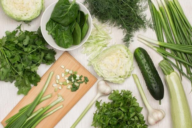 Satz grüns und gemüse. frühlingszwiebeln auf schneidebrett. kohl und zucchini, petersilie, dill und koriander auf dem tisch. weißer hintergrund. flach legen