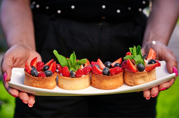 Satz hausgemachte kuchen mit blaubeeren, erdbeeren und minze auf einem teller