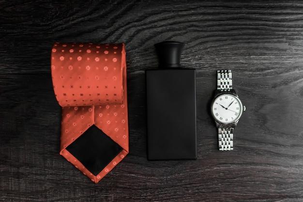 Satz herrenaccessoires, uhren, krawatte, parfums auf einem hölzernen dunklen hintergrund.