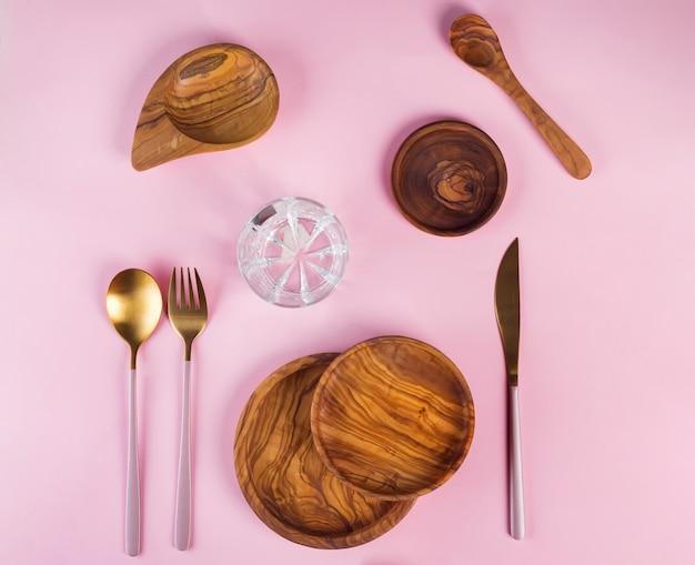 Satz hölzerne küchengeräte gemacht vom olivenholz mit goldenem luxusbesteck auf rosa, flacher lage