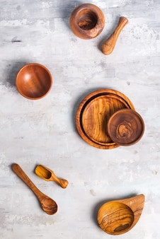 Satz hölzerne küchengeräte hergestellt vom olivenholz auf steinhintergrund, ebenenlage