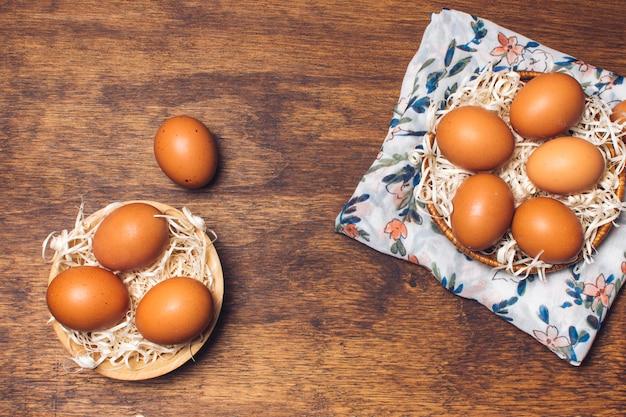 Satz hühnereien in den schüsseln auf geblühtem material an bord