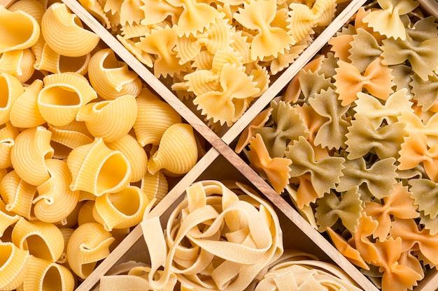 Satz italienischer teigwarenhintergrund mit rohrrigate, tagliatelle und farfalle