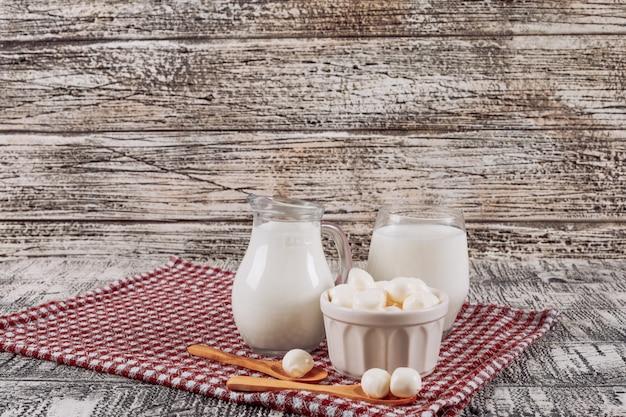 Satz käse und holzlöffel und flaschen milch auf grauem holz- und picknicktuchhintergrund. seitenansicht. platz für text