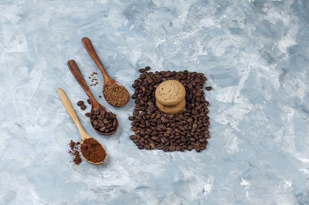 Satz kaffeebohnen, instantkaffee, kaffeemehl in holzlöffeln und keksen auf hellblauem marmorhintergrund. high angle view.