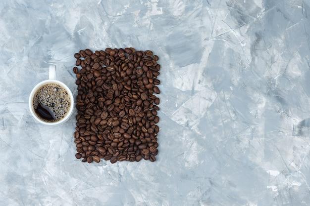 Satz kaffeebohnen und kaffee in einer tasse auf einem blauen marmorhintergrund. draufsicht.