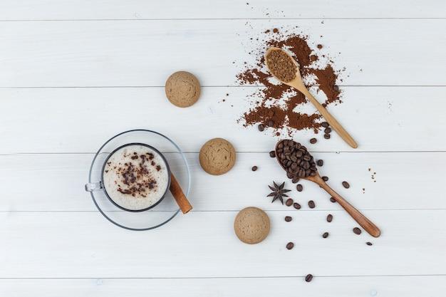 Satz kekse, gemahlener kaffee, kaffeebohnen, zimtstange und kaffee in einer tasse auf einem hölzernen hintergrund. flach liegen.