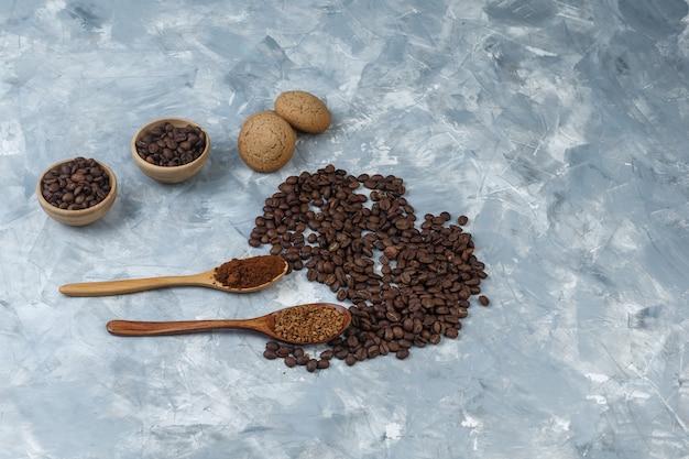 Satz kekse, instantkaffee und kaffeemehl in holzlöffeln und kaffeebohnen in schalen auf hellblauem marmorhintergrund. nahansicht.