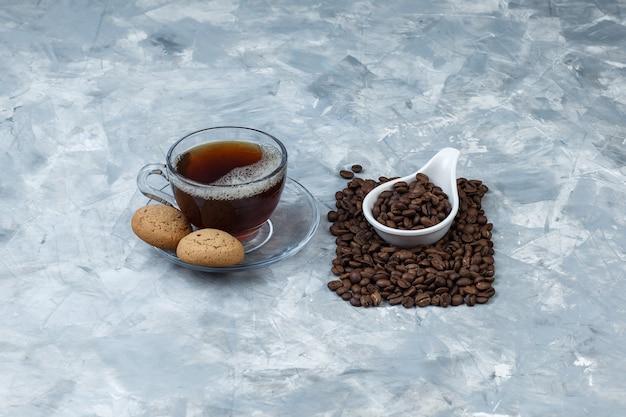 Satz kekse, tasse kaffee und kaffeebohnen in einem weißen porzellankrug