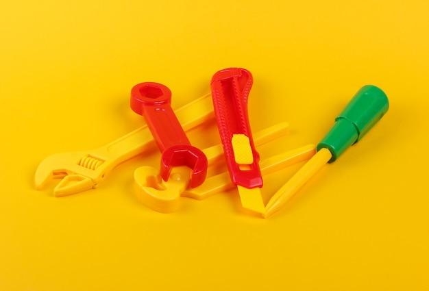 Satz kinderspielzeugarbeitswerkzeuge auf gelb.
