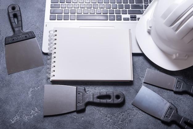 Satz kittmesser und helm auf grauem hintergrund