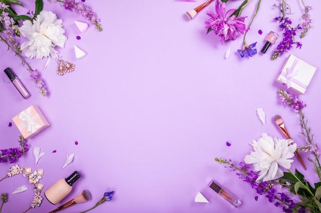 Satz kosmetik, bürsten und schmuck mit frischen blumen auf purpur. sommerschlussverkauf. einkaufen