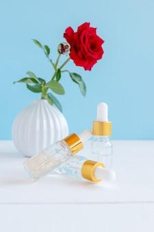 Satz kosmetischer glasflaschen mit einer pipette auf einem hölzernen hintergrund mit roter rose. naturkosmetikkonzept, natürliches ätherisches öl mit 24k goldeinschlüssen.