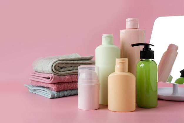 Satz kosmetischer hautpflegeprodukte, gesichtsprodukte, leere flaschenverpackungen der hautpflege auf rosa hintergrund. beauty- und spa-konzept.
