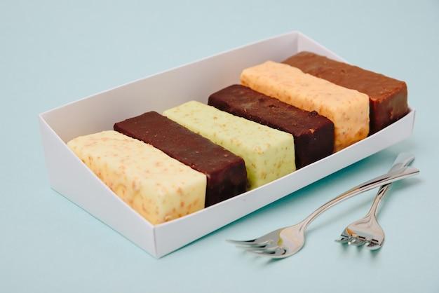 Satz kuchen in zuckerguss und schokolade auf einer hellen oberfläche