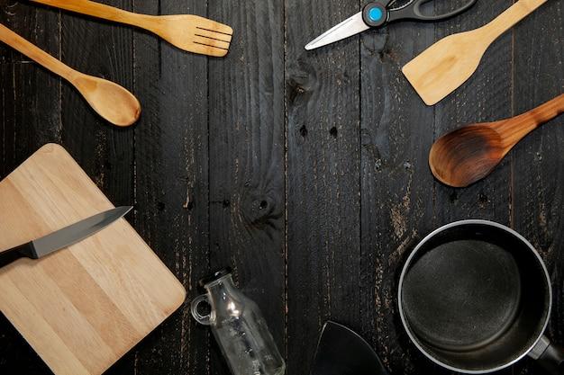 Satz küchengeschirr auf dem schwarzen hölzernen hintergrund