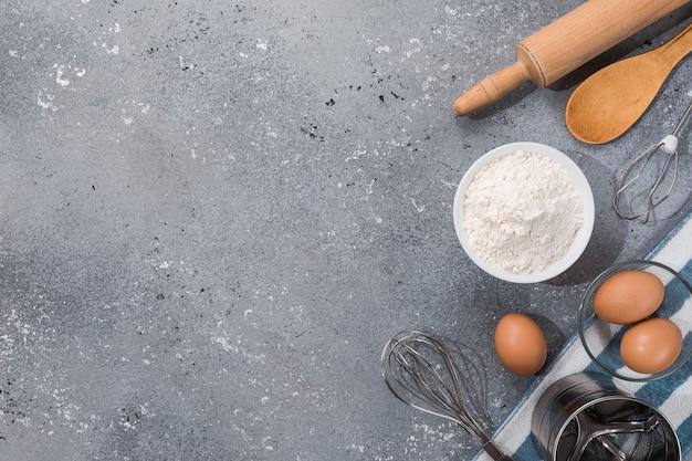 Satz küchenutensilien mit produkten auf grau-blauem hintergrund. meisterkurse kochen. speicherplatz kopieren.