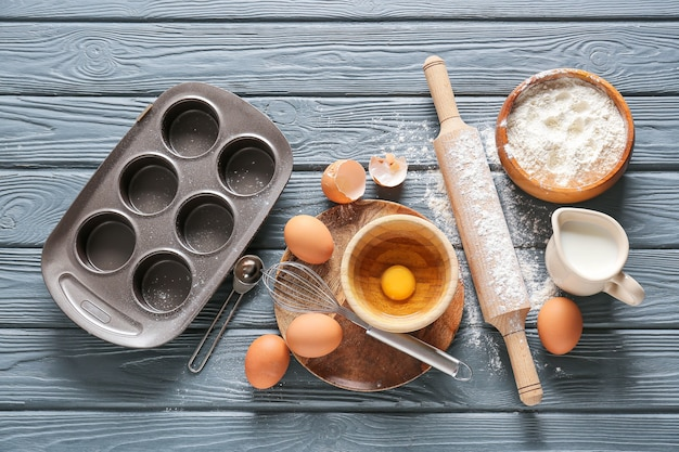Satz küchenutensilien und zutaten für die zubereitung der bäckerei auf dunklem hölzernem hintergrund