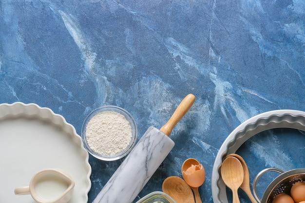 Satz küchenutensilien und zutaten für die zubereitung der bäckerei auf farbigem hintergrund