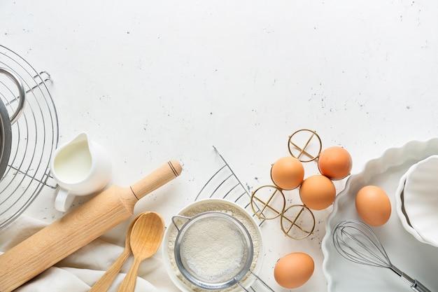 Satz küchenutensilien und zutaten für die zubereitung der bäckerei auf hellem hintergrund