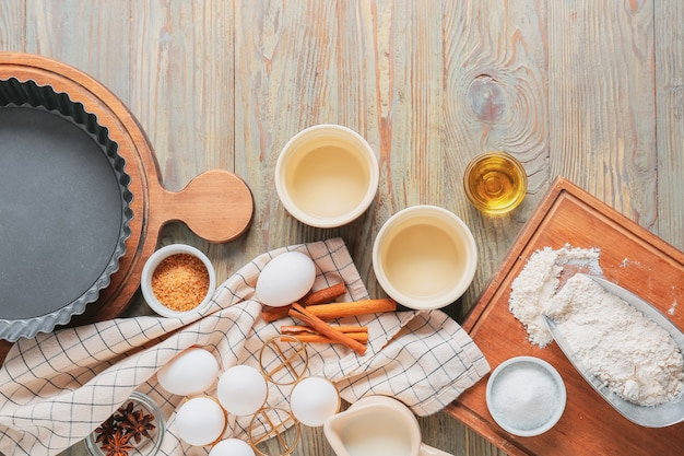 Satz küchenutensilien und zutaten für die zubereitung der bäckerei auf hölzernem hintergrund