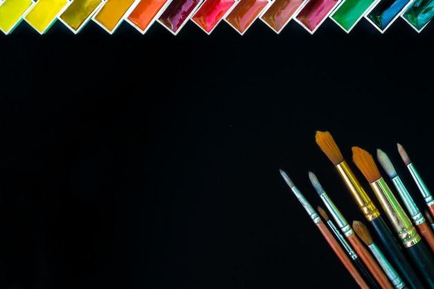 Satz künstlerische bürsten und aquarellpalette auf schwarzem hintergrund mit raum für text