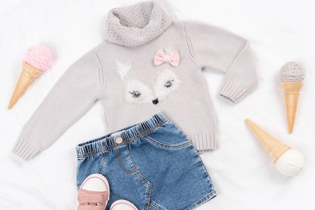 Satz lässige kinderkleidung, schuhe und accessoires auf weißem hintergrund. mode mädchen lookbook-konzept. strickpullover, jeansrock, turnschuhe, eistüte. ansicht von oben, flach.