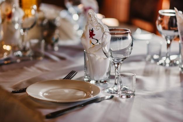 Satz leere gläser und teller mit tischbesteck auf einer weißen tischdecke auf dem tisch im restaurant