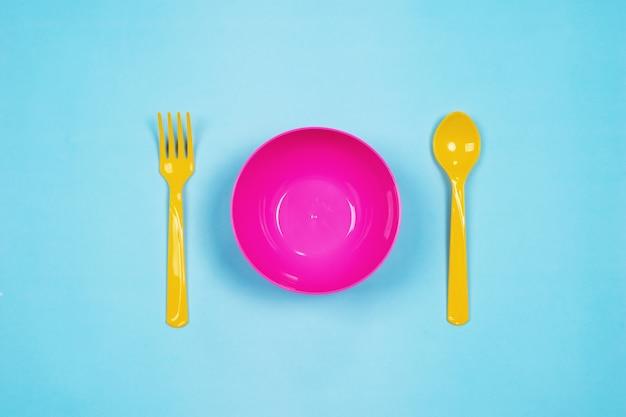 Satz leere rosa plastikgeschirrschüsseln, gelbe löffel und gabeln