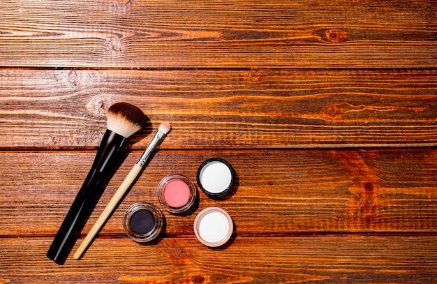 Satz make-up-pinsel und matte lidschatten und erröten auf hölzernem hintergrund