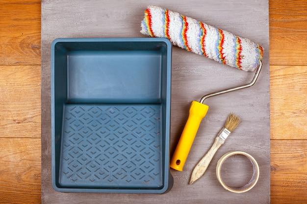 Satz malwerkzeuge auf grauem hintergrund. tablett quastenrolle klebeband. von oben betrachten.