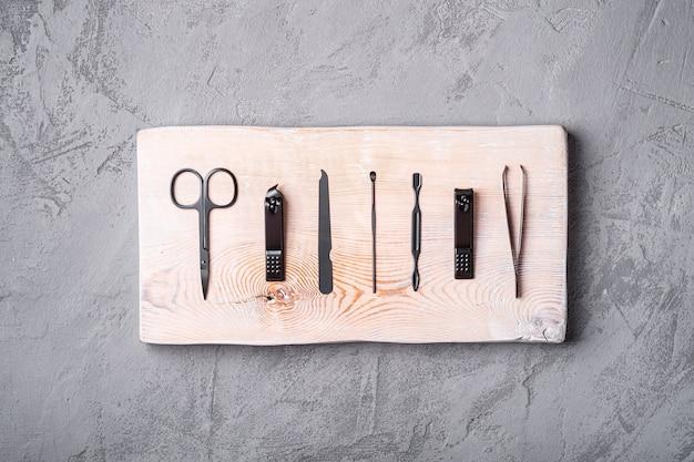 Satz maniküre, pediküre-werkzeuge und zubehör auf holzbrett, steinbeton, draufsicht