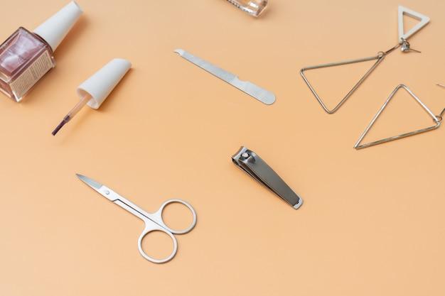 Satz maniküreinstrumente und -werkzeuge mit nagellack und frauenaccessoires auf orangefarbenem hintergrund, nahaufnahme