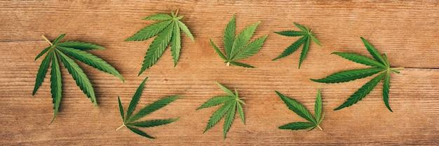 Satz marihuana-blätter, hanf von verschiedenen größen auf einem hölzernen hintergrund, fahne