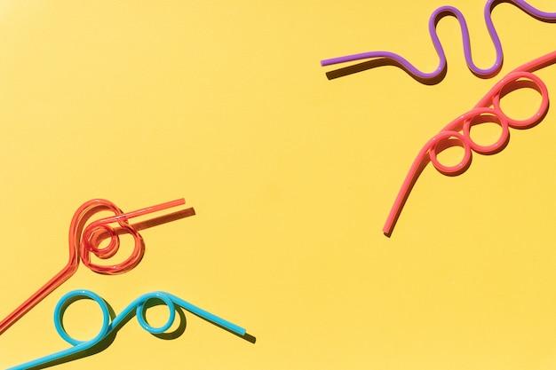 Satz mehrfarbige spiralcocktailröhrchen, lokalisiert auf gelbem hintergrund