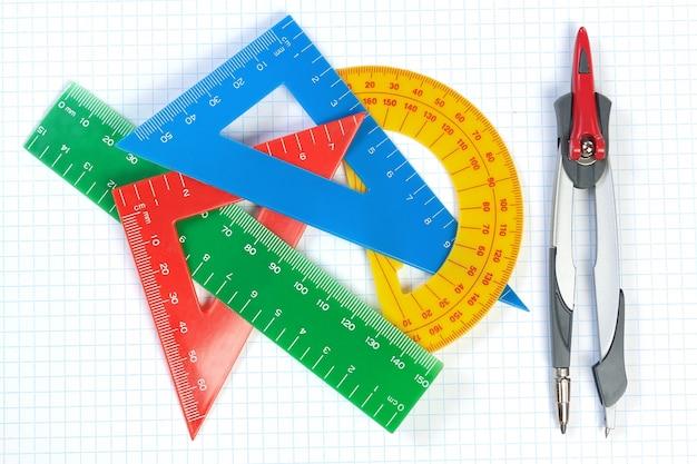 Satz mehrfarbiger linien aus dreiecken, winkelmessern und bremssattel. an einer weißen wand.