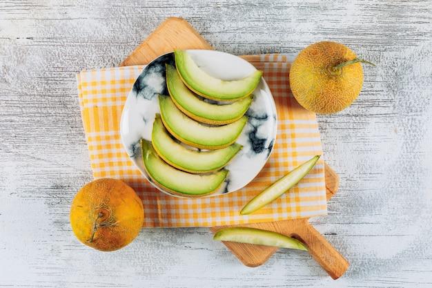 Satz melonen und geschnittene melone in einem teller auf einem strukturierten stoff und einem weißen steinhintergrund. flach liegen.