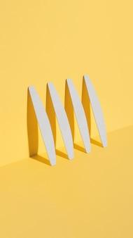 Satz nagelfeilen, schmirgelbrett für nägel unterschiedlicher formen und unterschiedlicher steifigkeit auf gelbem hintergrund. isometrische diagonalprojektion. minimal, trendige schatten, modernes foto. mock-up für maniküre
