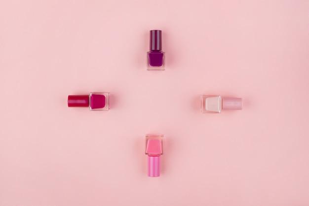 Satz nagellacke und blumen auf einer rosa wand. schönheitskonzept, flach lag mit platz für text.