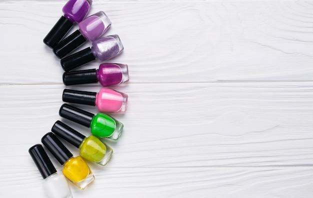 Satz nagellackflaschen in der unterschiedlichen farbe auf weißem hölzernem hintergrund
