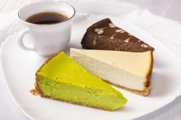 Satz new york, schokolade und pistazienkäsekuchen auf weißem teller und tasse kaffee. nahansicht.