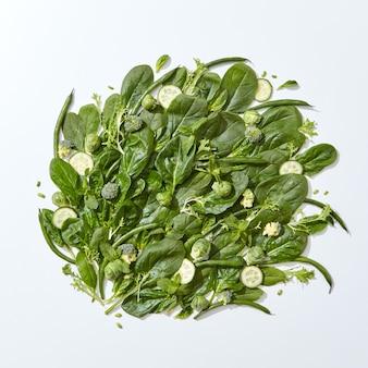 Satz organischer grüner spinat, minzblätter, brokkoli, spargel, rosenkohl und gurkenscheiben auf grauem hintergrund mit platz für text. vegetarisches gesundes essen. flach liegen