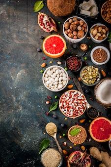 Satz organisches lebensmittel der gesunden diät, superfoods - bohnen, hülsenfrüchte, nüsse, samen, grüns, obst und gemüse. draufsicht des dunkelblauen hintergrundkopienraumes