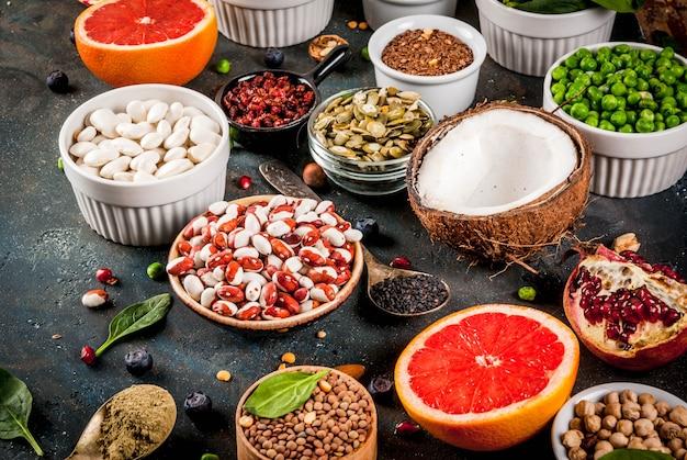 Satz organisches lebensmittel der gesunden diät, superfoods bohnen, hülsenfrüchte, nüsse, samen, grüns, obst und gemüse. dunkelblau